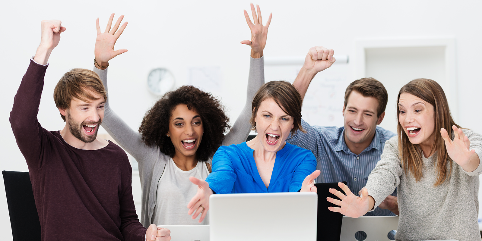 Office team celebrating as they look at a computer screen
