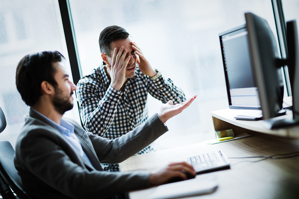 Two frustrated coworkers in an office look at a computer monitor with anger.