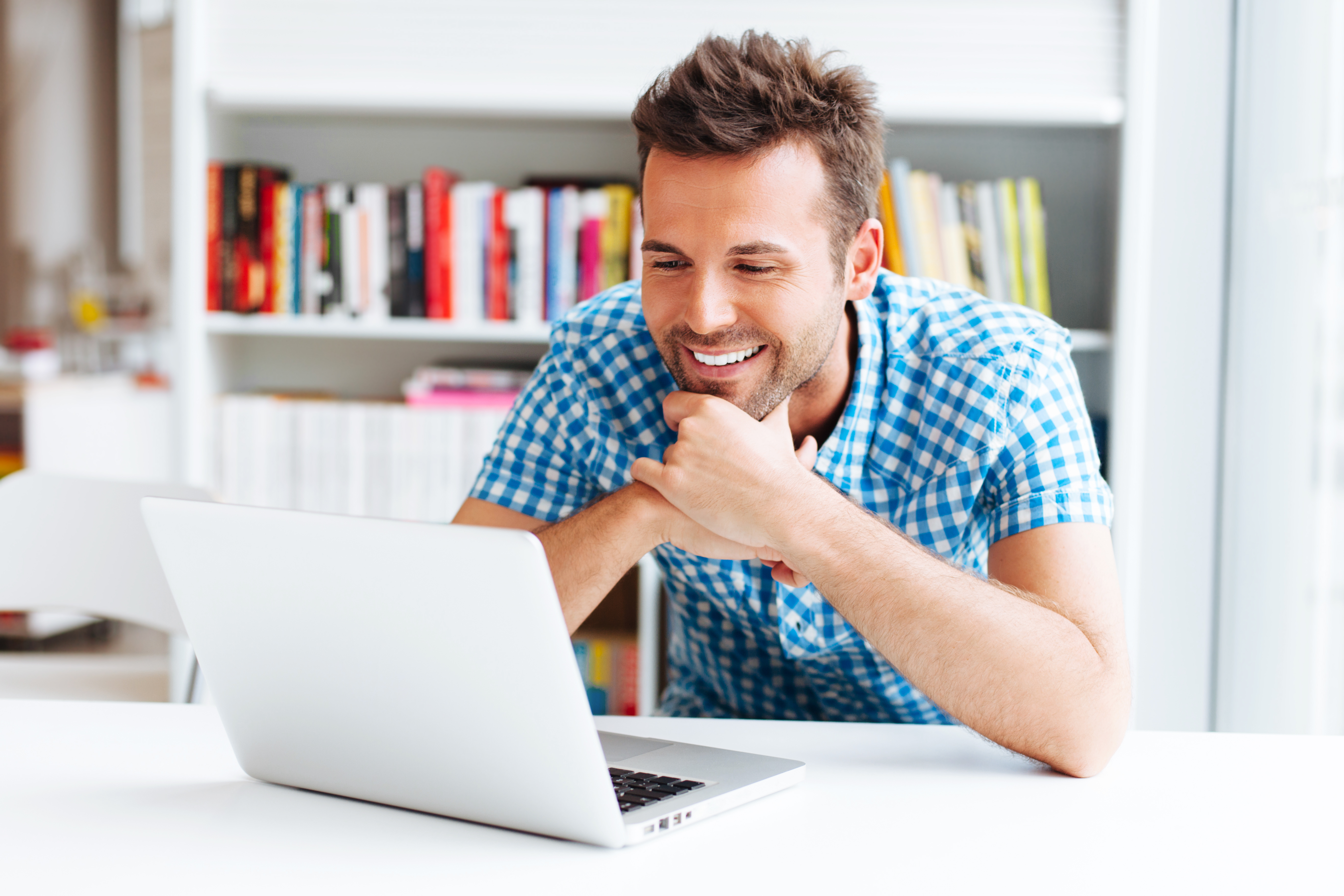 man in white office smiling as he looks at his laptop
