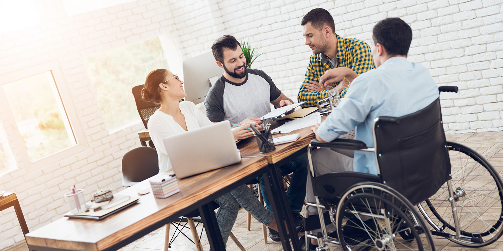 Four coworkers talk across a conference table, one of them is in a wheelchair